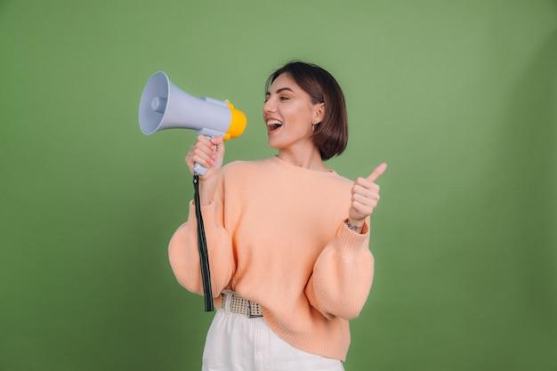 緑のオリーブ色の壁に分離されたカジュアルな桃のセーターの若い女性