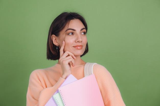 Молодая женщина в повседневном персиковом свитере изолирована на стене зеленого оливкового цвета