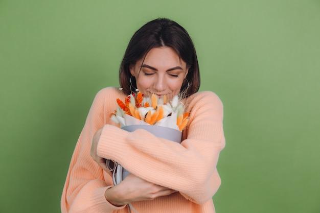 녹색 올리브 벽에 고립 된 캐주얼 복숭아 스웨터에 젊은 여자 목화 꽃 라든지 밀과 lagurus의 오렌지 흰색 꽃 상자 구성 선물 행복 놀란 놀란