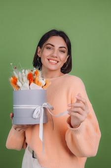 緑のオリーブの壁に分離されたカジュアルな桃のセーターの若い女性は、ギフトのための綿の花カスミソウ小麦とラグラスのオレンジ色の白いフラワーボックスの構成を保持します幸せな驚き驚き