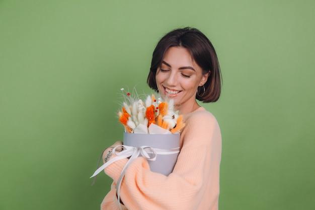 녹색 올리브 벽에 고립 된 캐주얼 복숭아 스웨터에 젊은 여자 목화 꽃 라든지 밀과 Lagurus의 오렌지 흰색 꽃 상자 구성 선물 행복 놀란 놀란 무료 사진