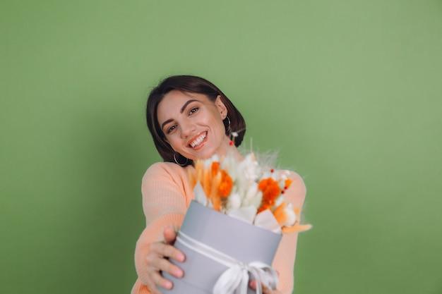 Молодая женщина в повседневном персиковом свитере, изолированном на зеленой оливковой стене, держит оранжевую белую цветочную коробку из цветов хлопка, гипсофилы, пшеницы и лагуру для подарка