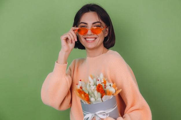 緑のオリーブの壁に分離されたカジュアルな桃のセーターの若い女性は、幸せな驚きの贈り物のために綿の花、カスミソウ、小麦、ラグラスのオレンジ色の白いフラワーボックスの構成を保持します