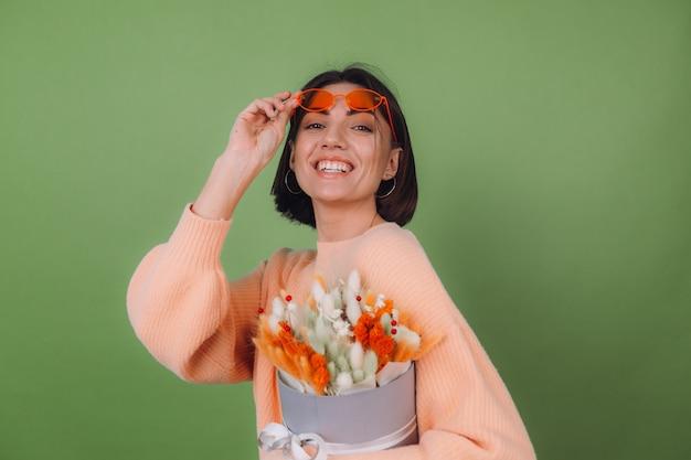 녹색 올리브 벽에 고립 된 캐주얼 복숭아 스웨터에 젊은 여자는 목화 꽃, 라든지, 밀, lagurus의 오렌지 흰색 꽃 상자 구성을 잡고 행복 놀라게 선물