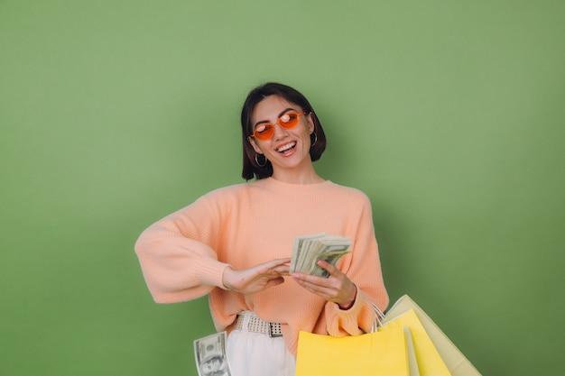Молодая женщина в повседневном персиковом свитере изолирована на зеленой оливковой стене, держа сумки для покупок, смеясь, бросая деньги в стороны в воздушной копии