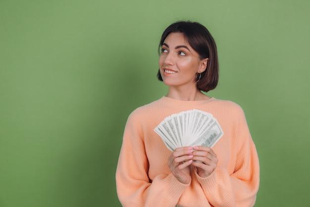 녹색 올리브 벽에 고립 된 캐주얼 복숭아 스웨터에 젊은 여자