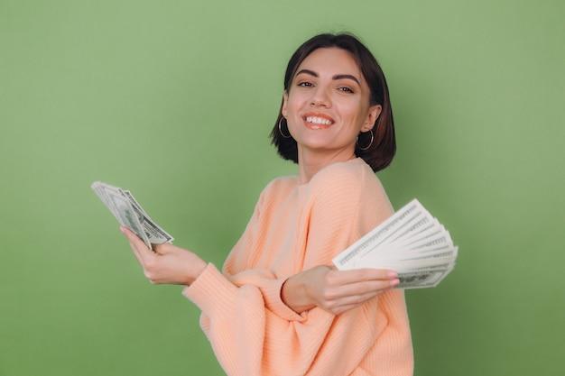 Молодая женщина в повседневном персиковом свитере изолирована на зеленой оливковой стене