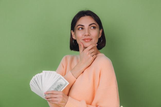 緑のオリーブの壁に分離されたカジュアルな桃のセーターの若い女性