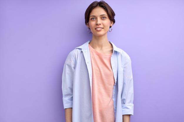 Молодая женщина в повседневной рубашке, глядя в камеру, позирует спокойно и уверенно, изолированные на фиолетовом фоне в студии