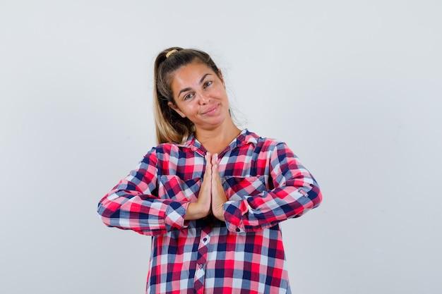 Молодая женщина в повседневной рубашке, показывающая жест намасте и обнадеживающая, вид спереди.