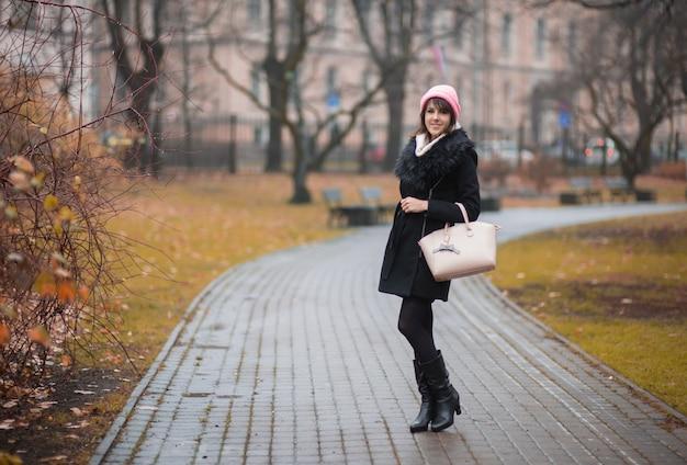 가을 도시 공원을 걷고 있는 캐주얼한 따뜻한 옷을 입은 젊은 여성