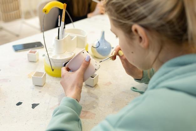 평상복을 입은 젊은 여성이 도자기 워크숍에서 찻잔에 장식품을 그립니다.