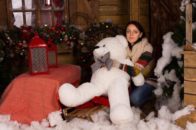 クリスマスの飾りで飾られた木造家屋で大きな白いクマの人形を抱きしめるカジュアルな冬の服装の若い女性。