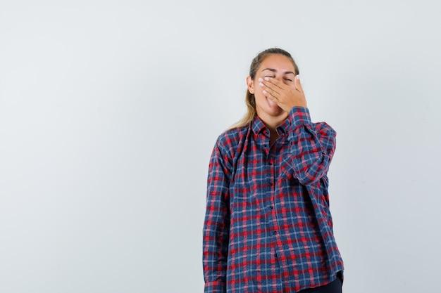 あくびをし、疲れているように見える間、手で口を覆うチェックシャツの若い女性