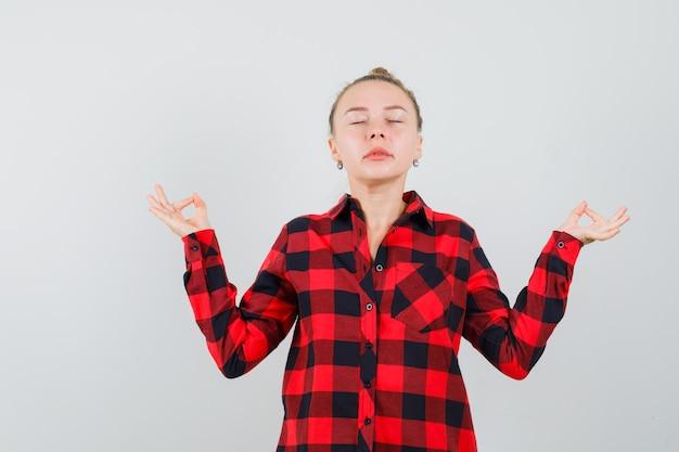 닫힌 된 눈으로 명상을하고 편안한 찾고 체크 셔츠에 젊은 여자