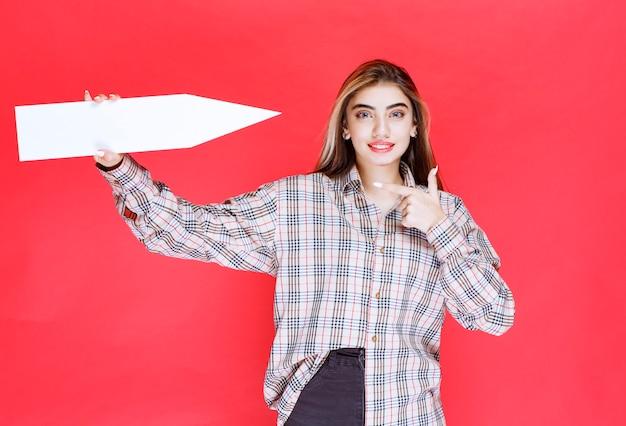 오른쪽을 가리키는 큰 화살표를 들고 체크 셔츠를 입은 젊은 여성