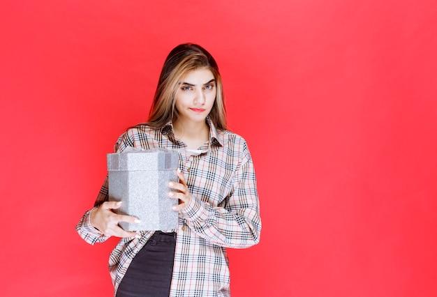 체크 셔츠를 입은 젊은 여성이 은색 선물 상자를 들고 혼란스럽고 사려깊게 보입니다.