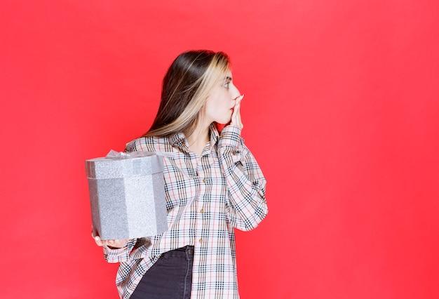 銀のギフトボックスを保持し、恐怖と恐怖に見えるチェックシャツの若い女性
