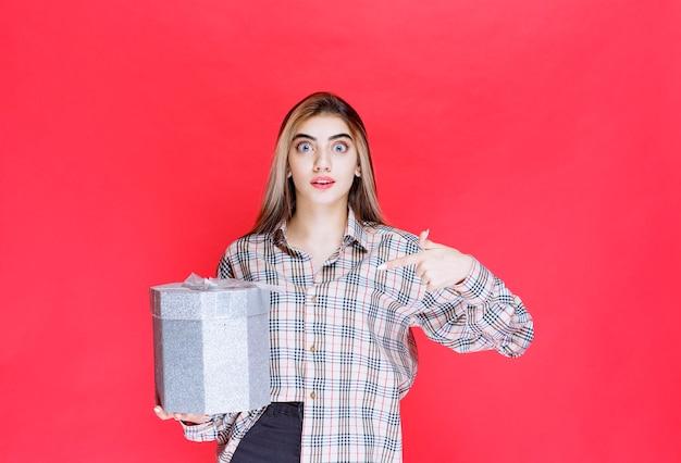 銀のギフトボックスを保持しているチェックシャツの若い女性