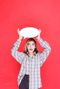 Молодая женщина в клетчатой рубашке держит информационную доску ovale
