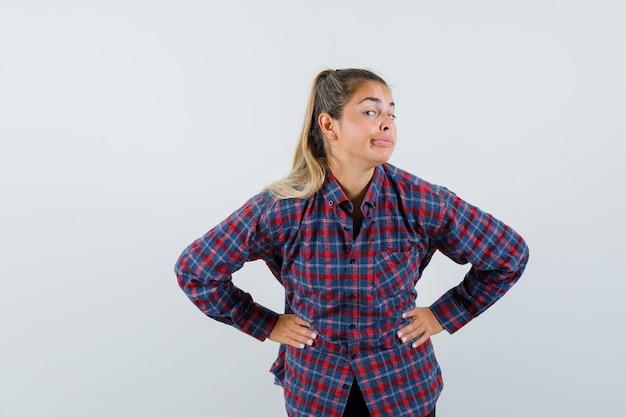 Молодая женщина в клетчатой рубашке, взявшись за руки на талии, улыбается и выглядит счастливой