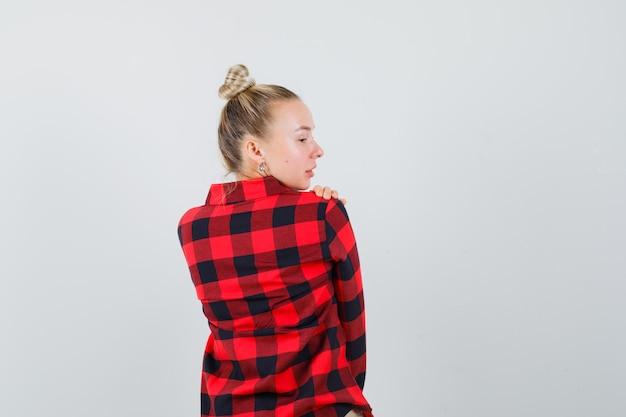彼女の肩越しに見て、魅力的に見えるチェックシャツの若い女性