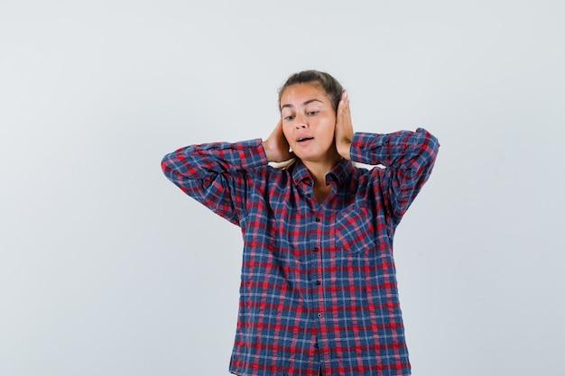 Молодая женщина в клетчатой рубашке сжимает руки уши и выглядит красиво