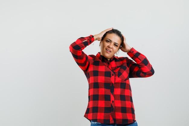チェックシャツを着た若い女性、手に頭を握りしめ、キュートに見えるショートパンツ、正面図。