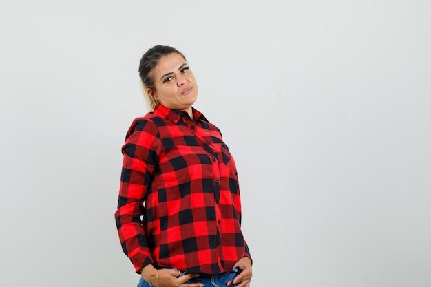 체크 셔츠에 젊은 여자, 서 있고 매혹적인, 전면보기 동안 포즈 반바지.