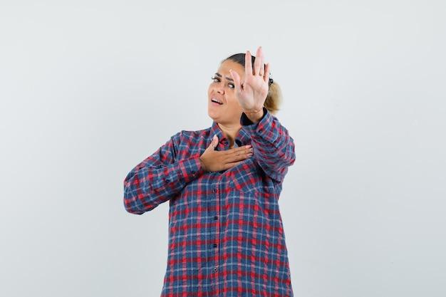 Молодая женщина в клетчатой рубашке показывает знак остановки и кладет руку на грудь и выглядит счастливой, вид спереди.