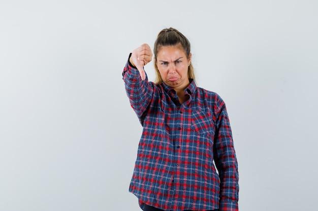 아래로 엄지 손가락을 보여주는 체크 셔츠에 젊은 여자와 불쾌 하 게 찾고 무료 사진