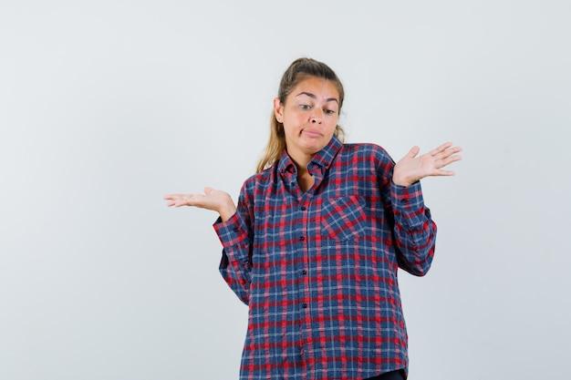 어깨를 으쓱하고 당황하는 체크 셔츠에 젊은 여자 무료 사진