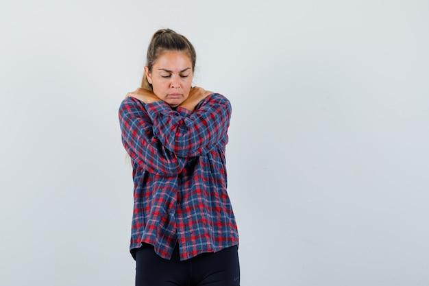 チェックシャツの立っている腕を組んで、寒さから震え、疲れ果てているように見える若い女性