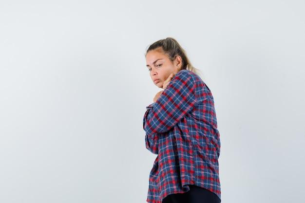 チェックシャツの立っている腕の若い女性は、肩越しに見て真剣に見ながら交差しました