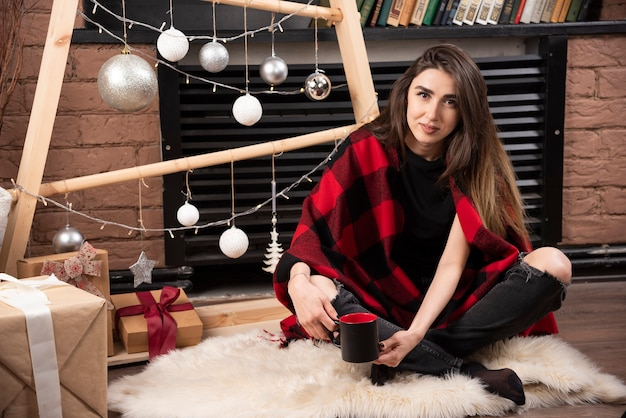 체크 무늬 격자 무늬 바닥에 앉아서 컵을 들고있는 젊은 여자.