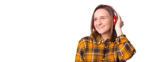 彼女の新しいヘッドフォンで音楽を楽しんでいる市松模様のシャツの若い女性