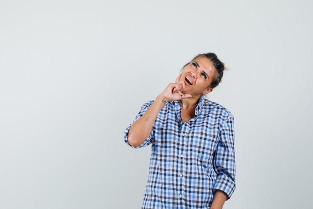 新しいアイデアを形成し、物思いにふける市松模様のシャツを着た若い女性。