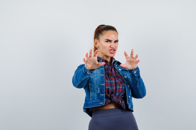 市松模様のシャツを着た若い女性、猫のように爪のジェスチャーをし、攻撃的に見えるジーンズのジャケット、正面図。