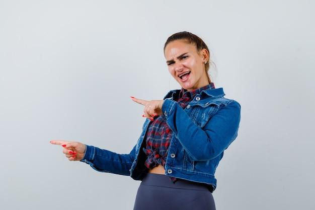市松模様のシャツを着た若い女性、横向きのジーンズジャケット、横向きで陽気に見えます。