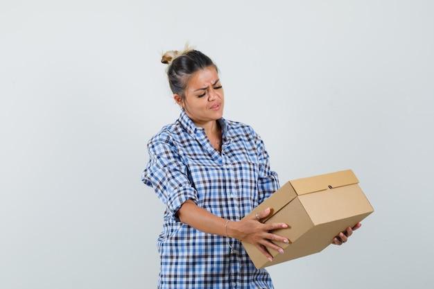 ボックスを見て、集中して見える市松模様のシャツの若い女性。