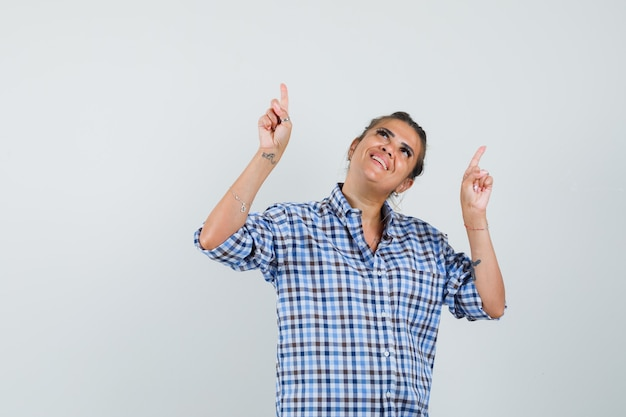市松模様のシャツを着た若い女性が上を向いて幸せそうに見えます。