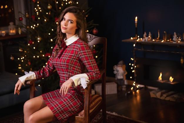 Молодая женщина в клетчатом теплом платье сидит у камина