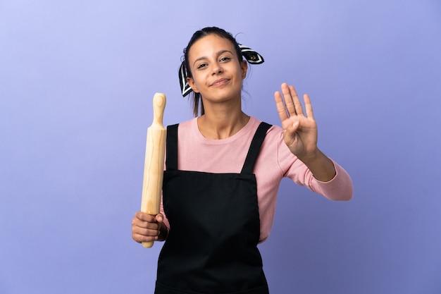 Молодая женщина в униформе шеф-повара счастлива и считает четыре пальцами
