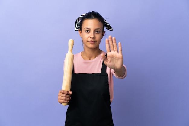 요리사 유니폼 만드는 중지 제스처에 젊은 여자
