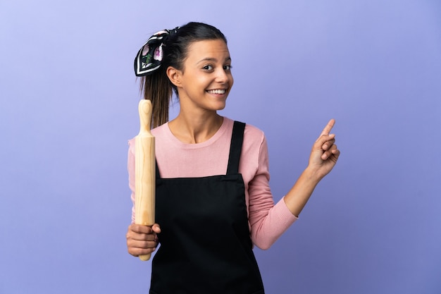 Молодая женщина в униформе шеф-повара, указывая назад