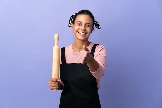 좋은 거래를 닫기 위해 악수하는 요리사 유니폼에 젊은 여자