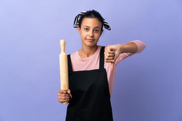 否定的な表現で親指を下に示すシェフの制服を着た若い女性