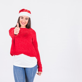 Young woman in Christmas hat with thumb up