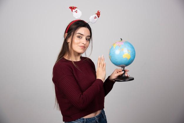 地球儀を保持しているクリスマスのヘッドバンドの若い女性。