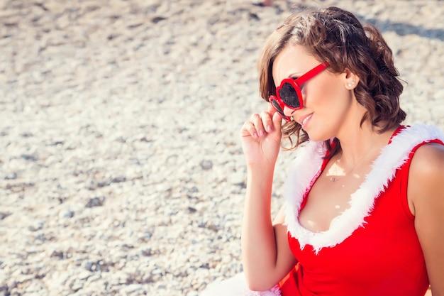 ビーチでクリスマススーツの若い女性